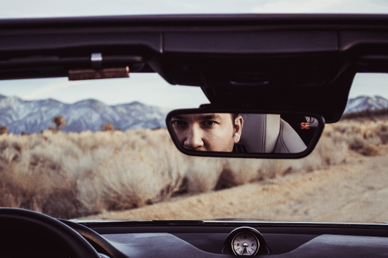 Man looking in the rear view mirror